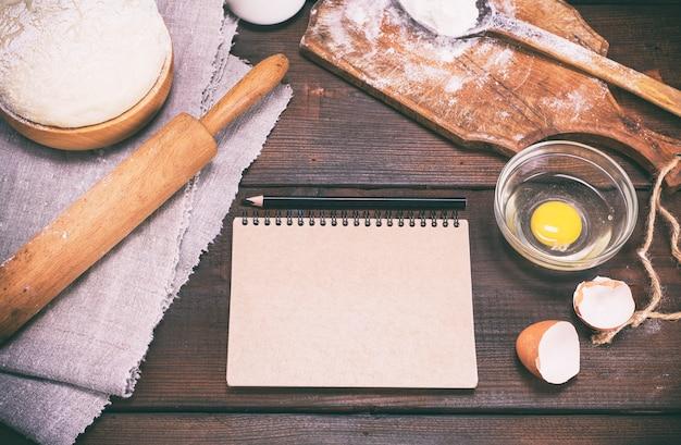 Бумажный блокнот с черным карандашом и тестом с ингредиентами