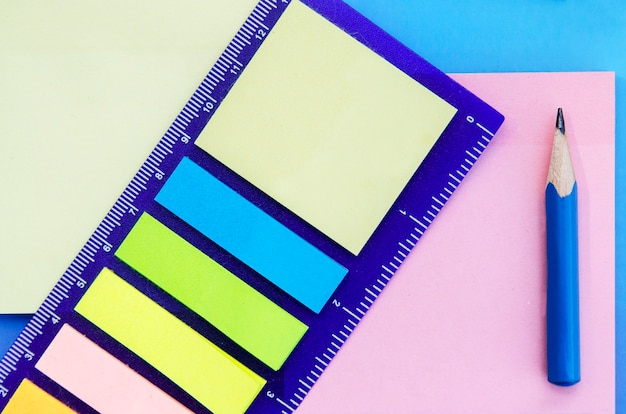Paper notes different colors with ruler and blue pencil. school supplies for new beginning