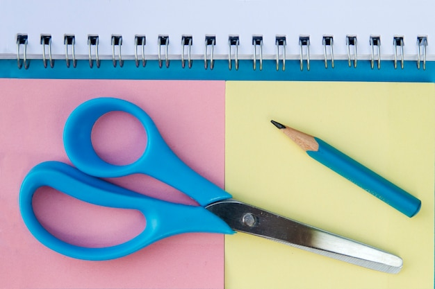 Paper notes, pencil and scissors from above. school accessories close up
