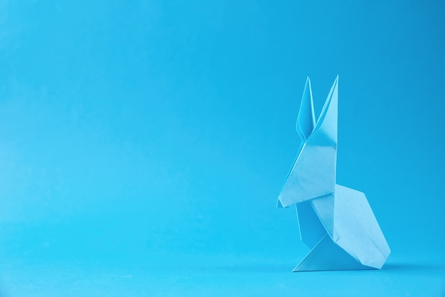 Paper origami esater rabbit on blue wall. easter celebration concept