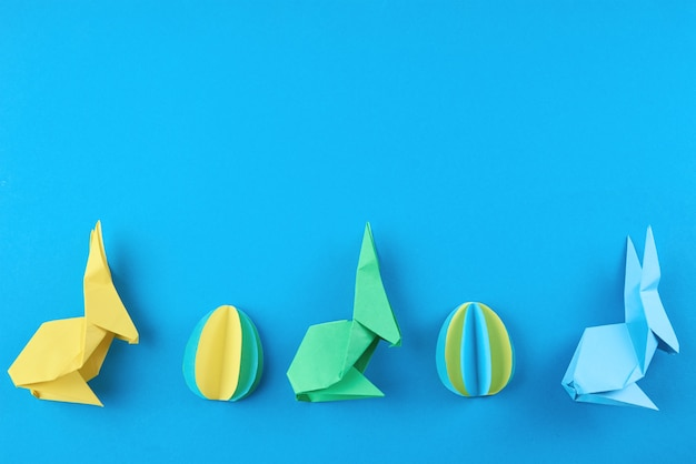 Paper origami esater rabbits and colored eggs on blue wall, top view. easter celebration concept