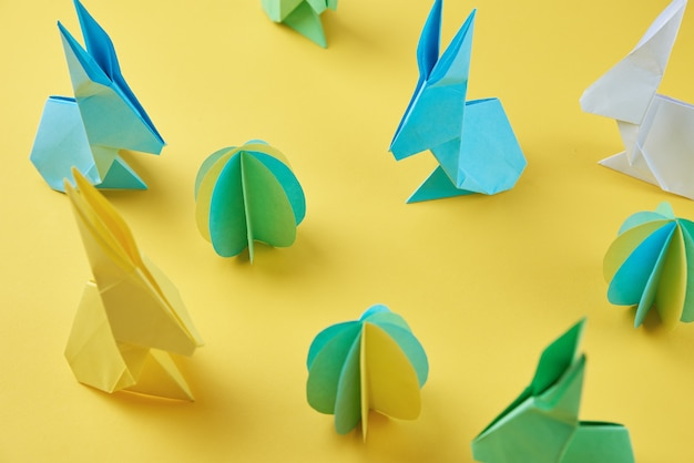 Paper origami esater rabbits and colored eggs on yellow wall, top view. easter celebration concept