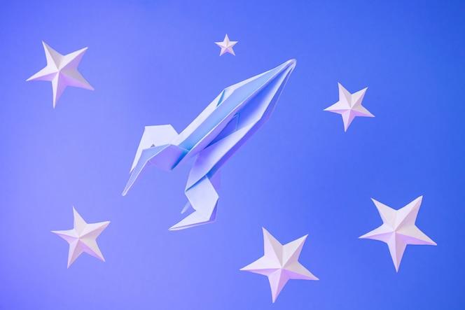 종이 접기 로켓 파란색에 종이 별 사이에서 날아