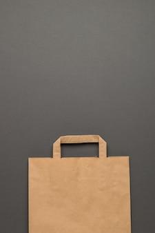 灰色の背景に紙の包装袋。テキスト用のスペース。フラットレイ。
