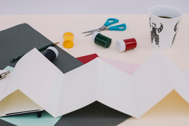 Paper and paint near coffee