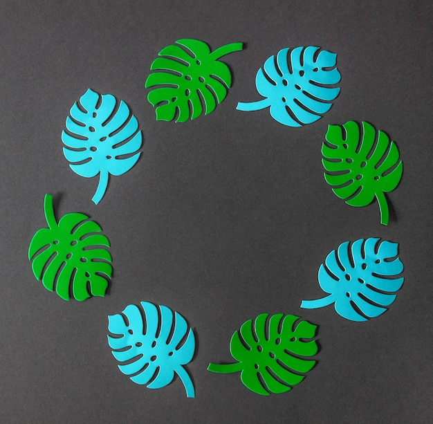 Бумажные пальмовые листья на зеленом фоне. минимальная концепция. плоская планировка.