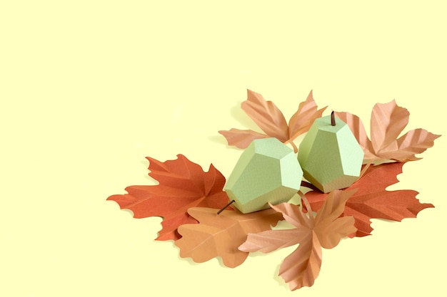 Paper pears and autumn leaves on yellow background