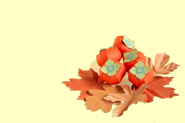 Paper persimmon and autumn leaves on yellow background