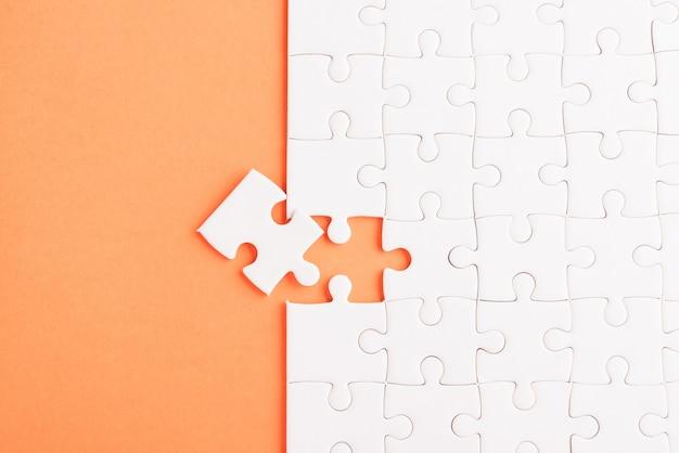 紙の無地の白いジグソーパズルゲームテクスチャの最後のピースを解決して配置する