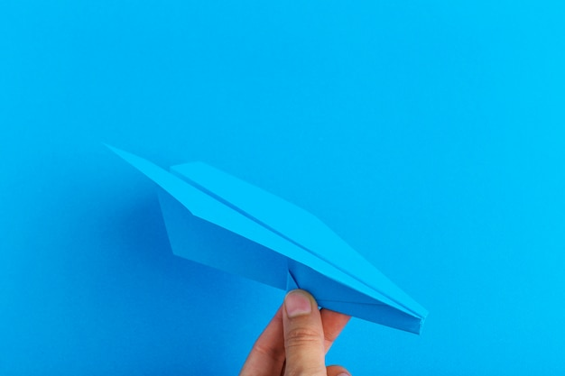 Paper plane on bright background holding in human hand. travel and tourism