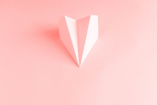 Paper plane on a coral background.