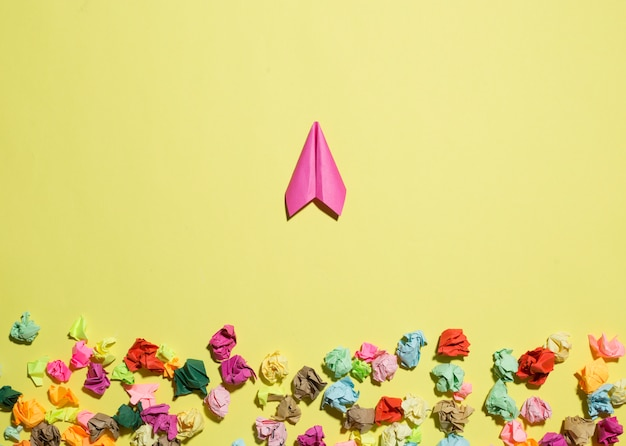 Paper plane flies away from crumpled stickers