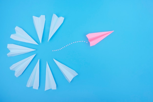 The paper plane flies in the opposite direction from the others.