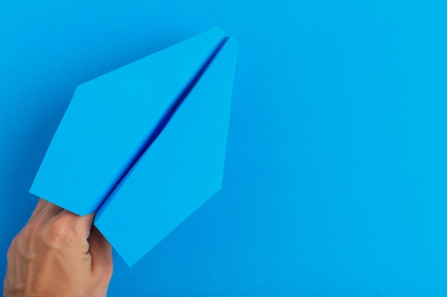 Paper plane holding in human hand. travel and tourism concept