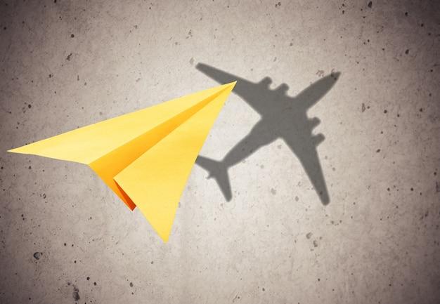 影のある飛行中の紙飛行機