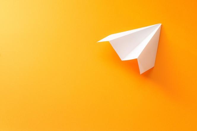 오렌지 배경에 종이 비행기