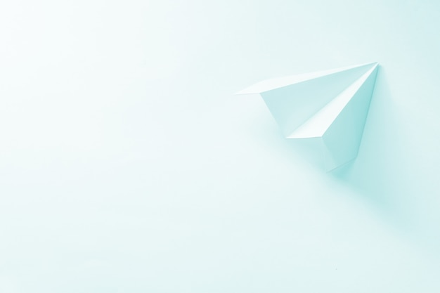 Paper plane on pale blue.