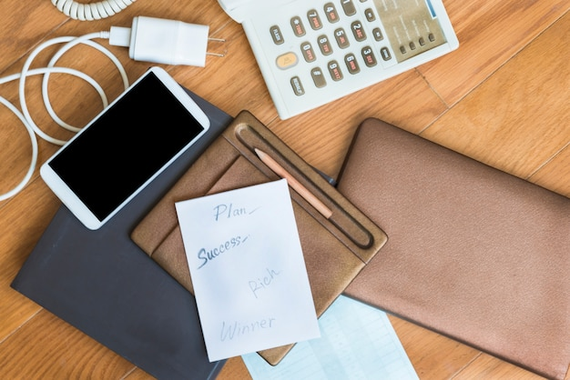 Paper plane to success on brown pad near pencil,smartphone,white charger,telephone on tabl