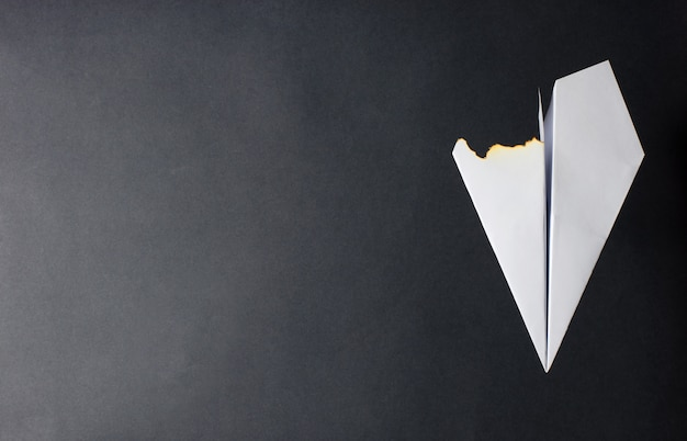 A paper plane with a burned wing. dark background. the concept of a fire on the plane or the crash.