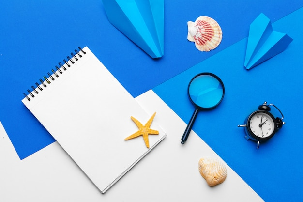 Paper plane with office supplies on blue background