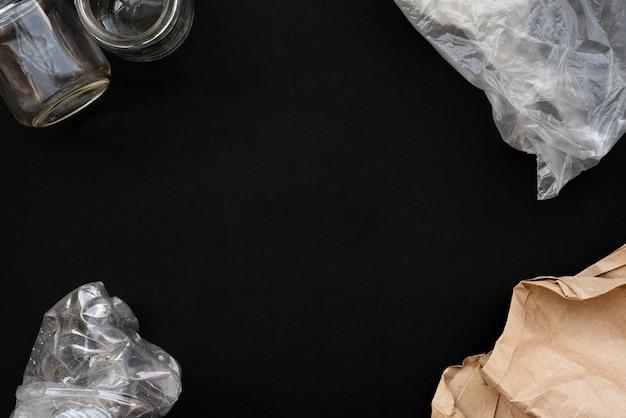 Отходы и мусор бумаги, пластика и стекла на черном фоне. переработка. скопируйте пространство.