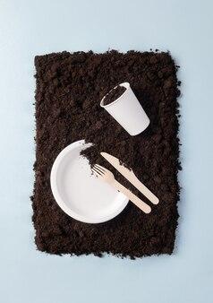 파란색 배경에 흙 위에 종이 접시와 유리, 나무 칼과 포크