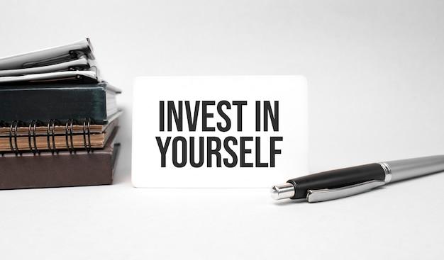종이 접시, 안경, 스택의 메모장, 펜 및 텍스트가 명함에 투자합니다.