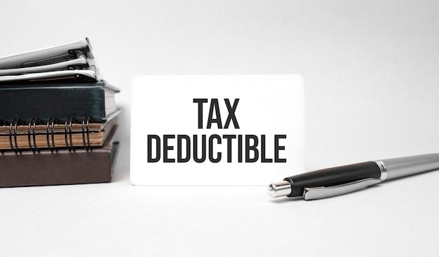Paper plate, glasses, notepad in stack,pen and text tax deductible on business card