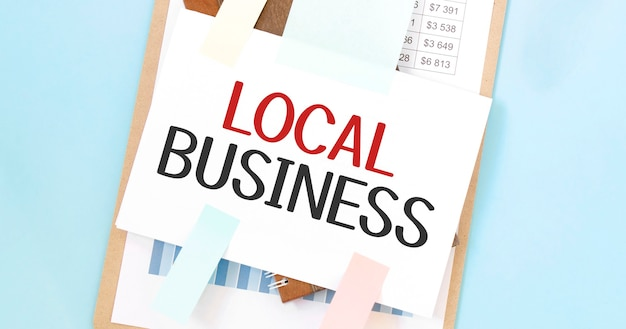 テキストローカルビジネスと紙皿。図、メモ帳、青い背景