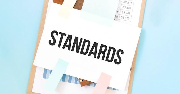 Бумажная тарелка с текстом стандарты. схема, блокнот и синий фон