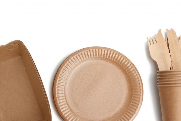 Бумажные тарелки и чашки из коричневой крафт-бумаги и деревянные вилки и ножи