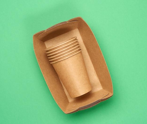 Бумажные тарелки и чашки из коричневой крафт-бумаги на зеленом фоне. концепция отказа от пластика, нулевые отходы