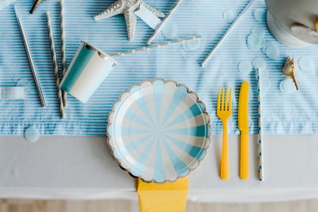 Бумажные тарелки на подготовленный день рождения таблицы для детей или девочек вечеринка в небесно-голубых и белых тонах. baby boy душ. крупным планом, вид сверху