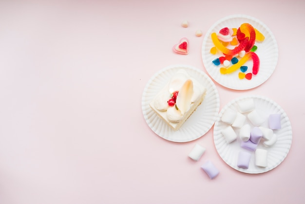 Paper plates with marshmallows; jelly candies and slice cake on pink background