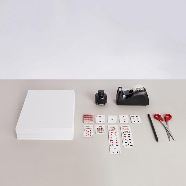 Carta, carte da gioco, forbici, una matita e un distributore di nastro adesivo su una superficie grigia
