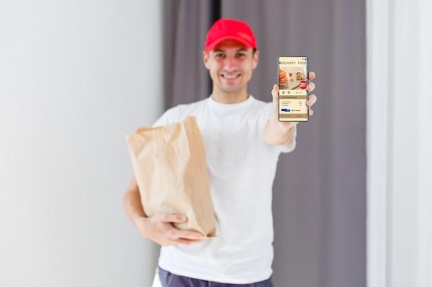 笑顔の配達員の手にある紙のポケットと食品容器。レストランの質の高いサービス。