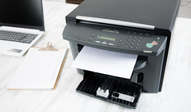 Paper in printer and computer on table