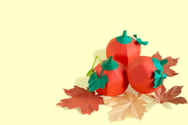 Paper pumpkins and autumn leaves on yellow background paper art and craft copy space