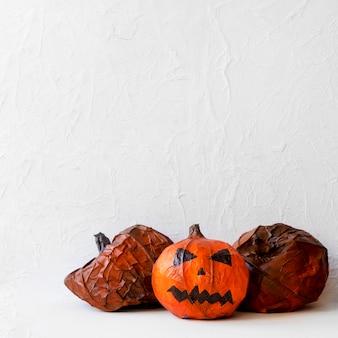 Paper pumpkins near spooky jack-o-lantern