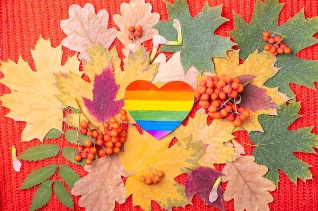 Бумажный символ лгбт-сердце радуги на разноцветных красных, оранжевых, зеленых сухих опавших осенних листьях и оранжевых ягодах рябины на красном фоне. осень - любимое время года