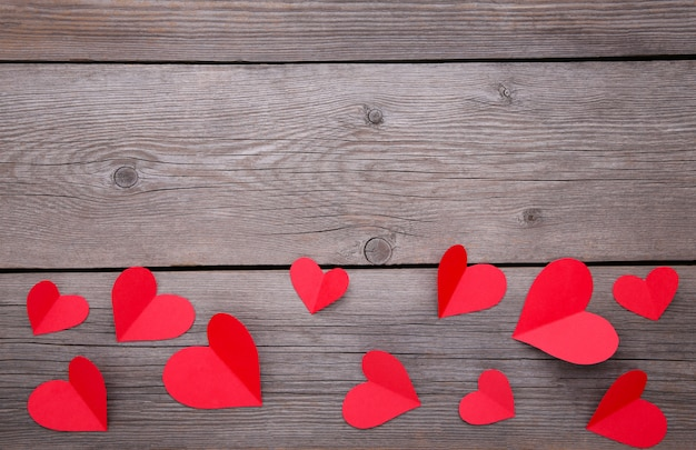 Paper red hearts on a grey background.