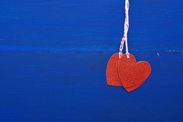 Бумажные красные блестящие декоративные сердечки висят на веревке на синем деревянном фоне