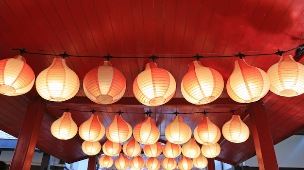 Paper red-white asian japanese lanterns in row glowing.