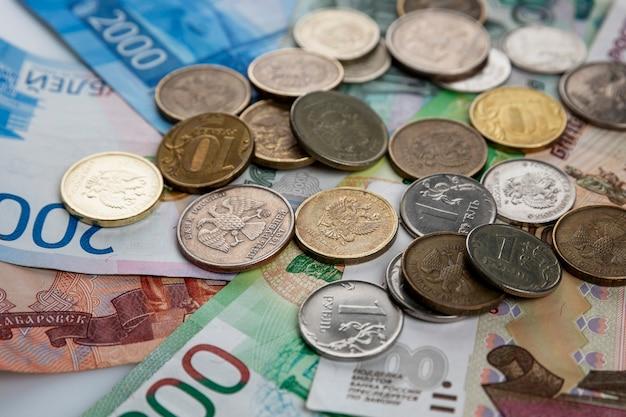 紙のルーブルとコインが山積みになっている