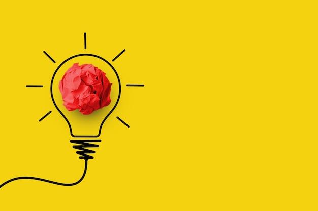 Бумажный мяч красного цвета с символом лампочки на желтом фоне