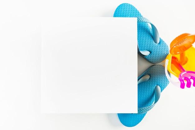 Бумажный лист возле флип-флопов и игрового комплекта