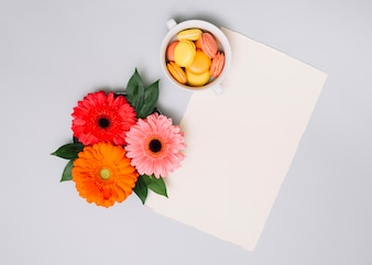 Paper sheet with small cookies and flowers on table