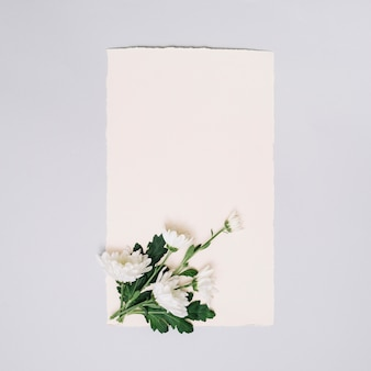 Paper sheet with small flowers on white table