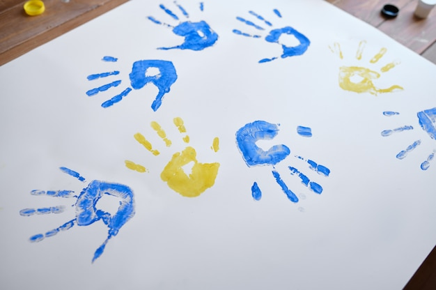 Лист бумаги с отпечатками детских ладошек, малыш веселится в мастерской. урок в художественной школе. работа молодого творческого художника, приятное хобби, счастливое детство.