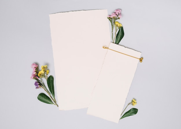 Paper sheets with small branches on white table